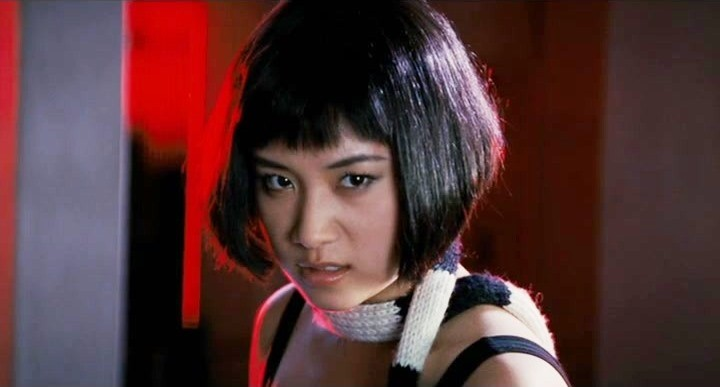 A close up of Knives as she prepares to fight. She is wearing a think black and white scarf and is surrounded by red lighting.