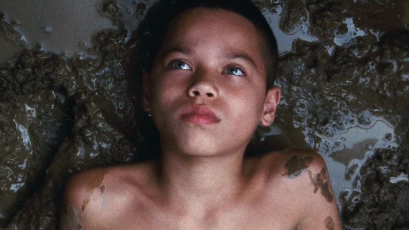 A young boy lays in the mud, looking up away from the camera. His chest is bare, and some of the mud has splashed onto his shoulders.