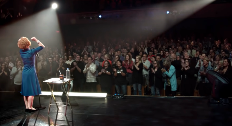 Kathy Griffin stands in a blue dress in front of a packed theater audience with her fist raised. Two spotlights are directed at her, and she has a small table next to her with paper and a water bottle.
