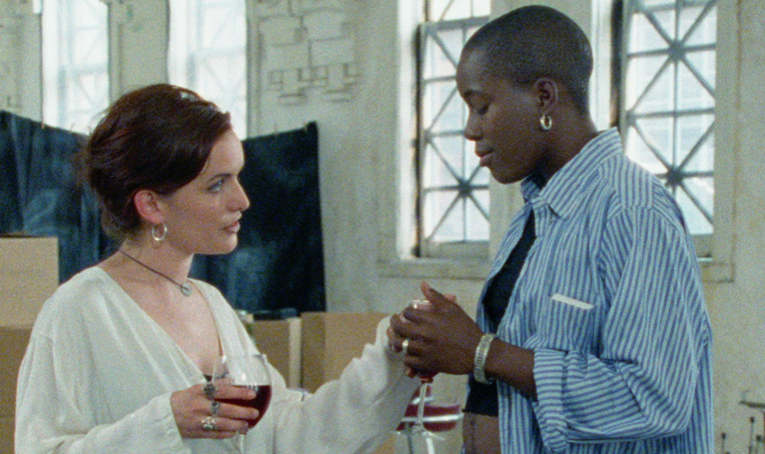 Two women stand in a large, warehouse-like apartment with tall skinny windows and art supplies in the background. The women are White and Black, respectively. The White woman is handing a glass of red wine to the Black women, who accepts it with a smile.