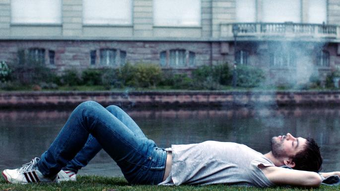 Leo lying on his back, smoking, by the canal