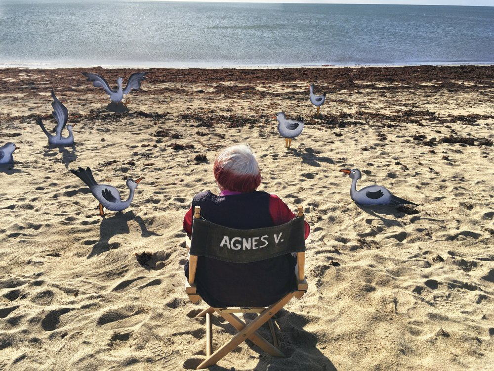 Agnes Varda sat in her director chair, on the beach with wooden seagulls spread around the sand. she looks out on the still ocean