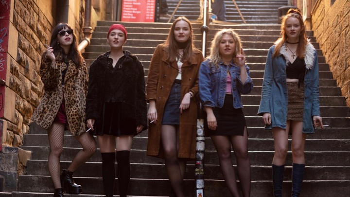 All five young women standing at the bottom of a tall set of stairs