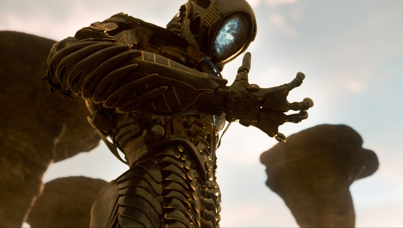 A humanoid robot with an ovular face looks down at his own hand. His face is a curved screen, and displays a blue galaxy-like pattern. Behind the robot are tall, curved, rock structures and a light blue sky.