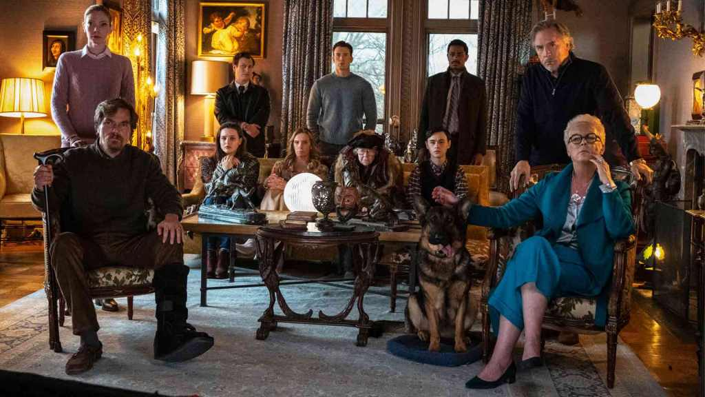 The full cast of the film Knives Out standing and sitting inside the lounge of a large country home.