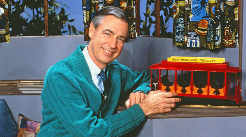 a shot of Mr Rogers with a toy train set on the set of his tv show