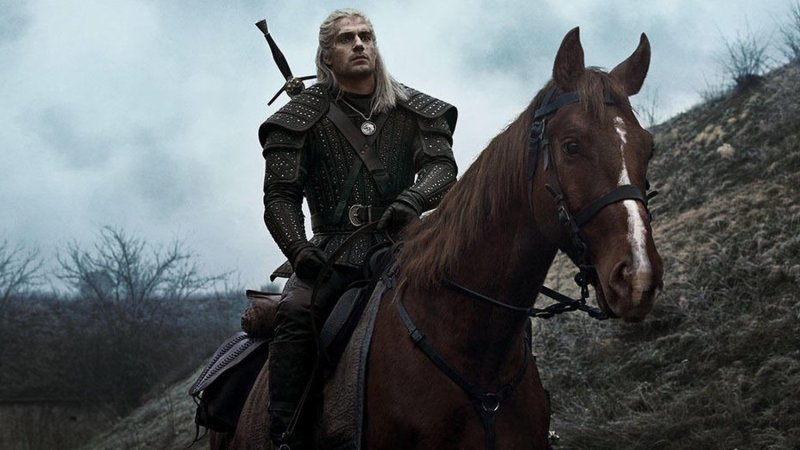 Henry Cavill in The Witcher is riding on top of a horse in a set of armor.