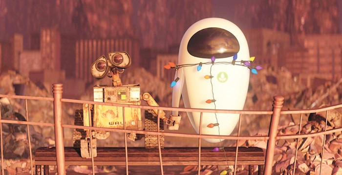 Screencapture from Wall-E. Two robots, one dirty and old and the other clean and new hold hands in a deserted wasteland.
