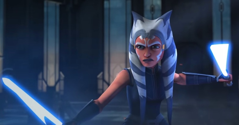 Ahsoka Tano is raising two blue lightsabers into a fighting position in Star Wars: The Clone Wars.