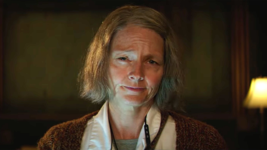 This image is a still from Hotel Artemis. The photo is a close up of Jodie Foster wearing make up to make her look much older.