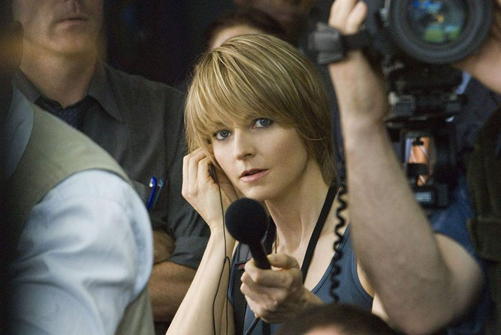 This image is a still from The Brave One. Jodie Foster is looking at the camera, holding up a microphone and listening through an earphone.