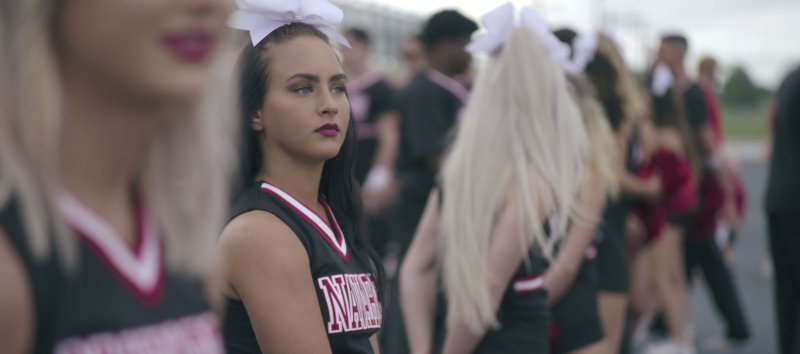 Cheerleader Gabi Butler looks out into the distance, dressed in her Navarro Cheer uniform.