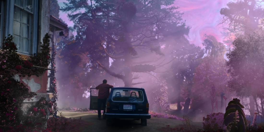 An image from the film Color out of Space. Nicolas Cage stands beside his car door, watching in horror as a purple haze engulfs and mutates his garden.