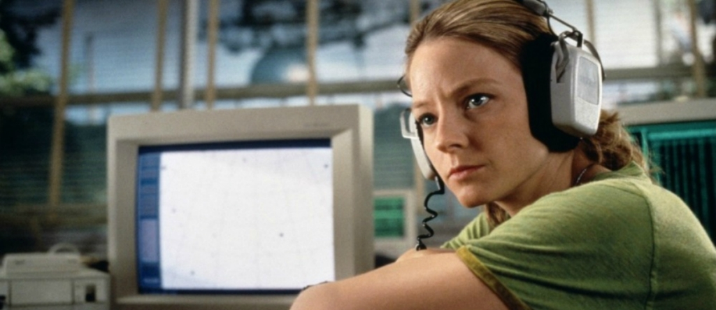 This image is a still from Contact. Jodie Foster is sitting next to a computer and wearing headphones.