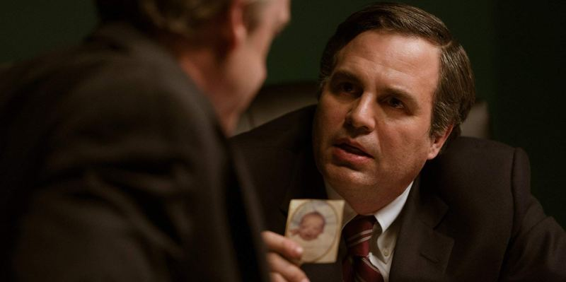 Mark Ruffalo in the film Dark Waters. A corporate attorney shows to another man a distressing photo of a baby with deformities.