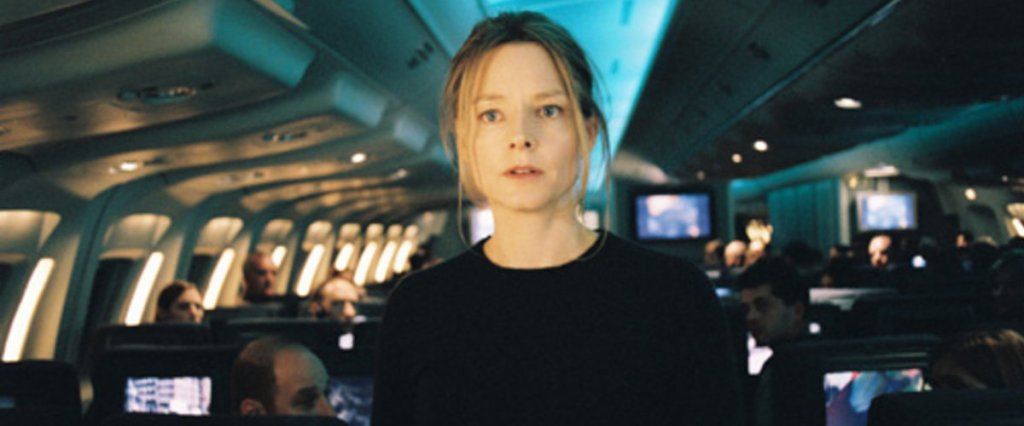 This image is a still from Flightplan. Jodie Foster is looking in the camera's direction and standing in an airplane aisle.
