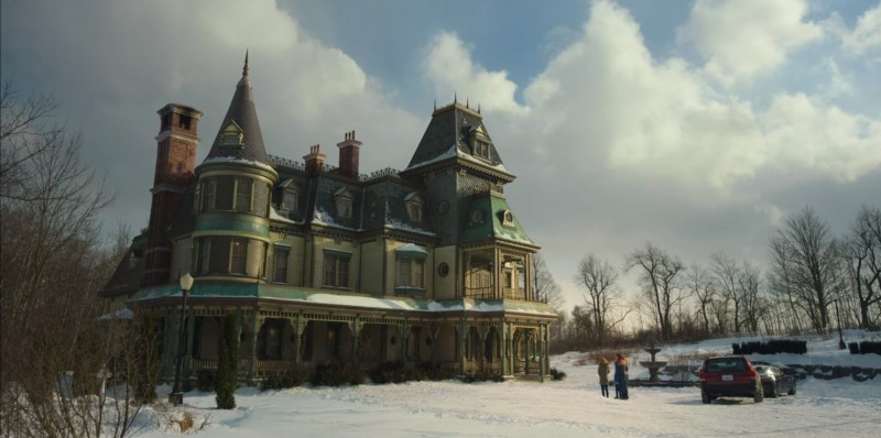 Image from the show Locke and Key. A wide shot of a family standing outside a Gothic mansion in the snow.
