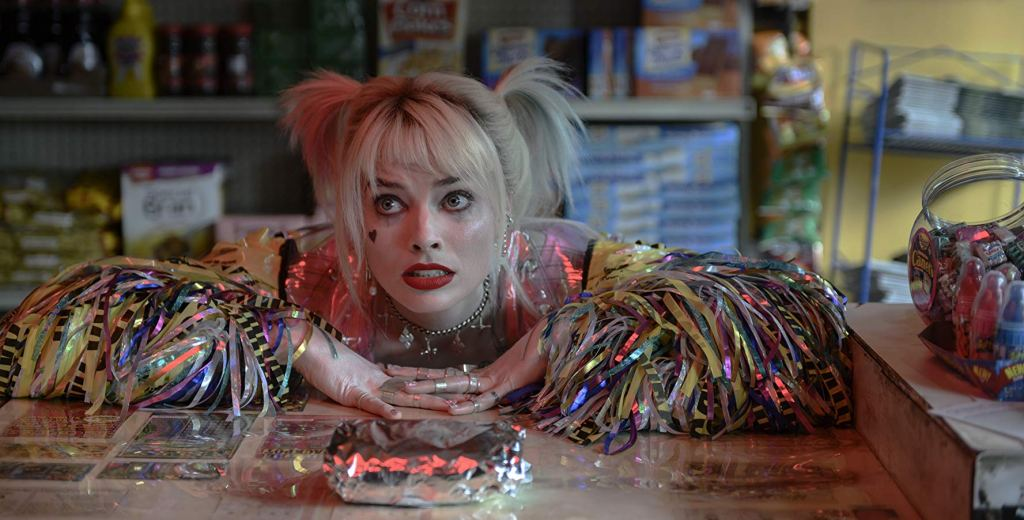 Harley Quinn leaning on the counter, her brunch sandwich in front of her