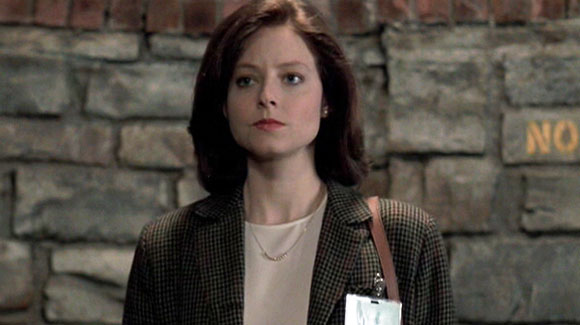 This image is a still from Silence of the Lambs. A younger Jodie Foster is wearing smart clothing, there is a brick wall behind her.