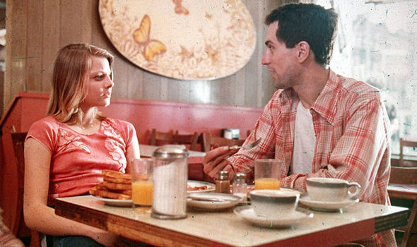 This image is a still from Taxi Driver. A young jodie foster is sitting at a breakfast dinner table and talking to Robert De Niro. There is tea, orange juice, and toast on the table.