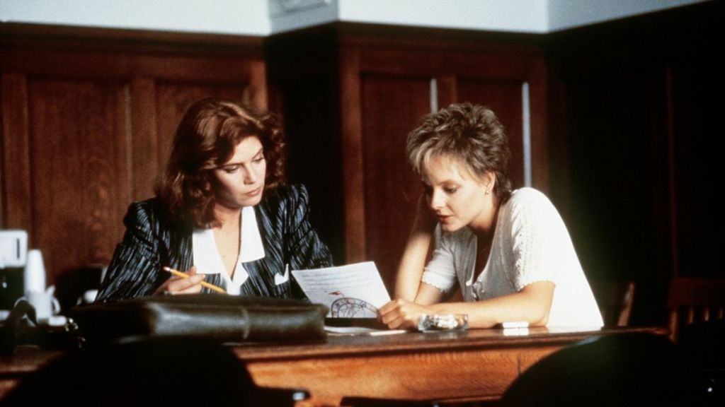 Kelly McGillis dressed as a lawyer while Jodie Foster is reading a legal document