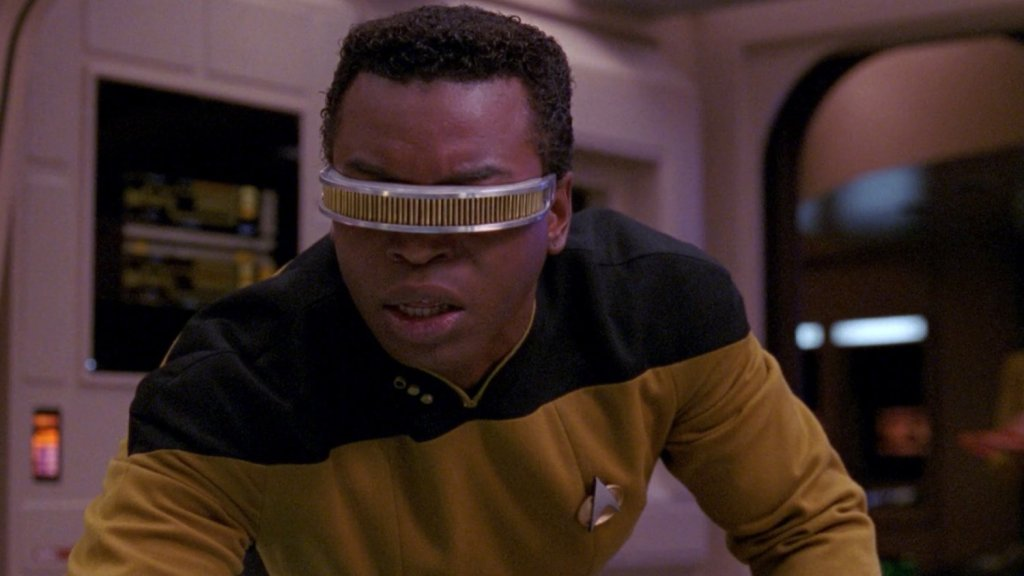 Close up image of La Forge wearing his VISOR, a futuristic band that wraps from one side of his face, over his eyes and to the other side of his face.