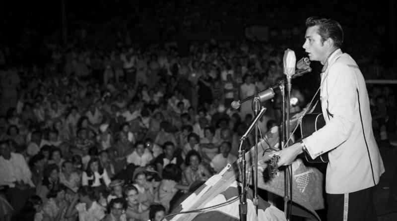 A man is playing the guitar and singing to a crowd of people in this black and white photograph.