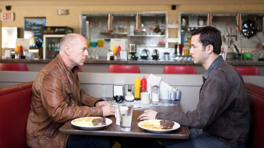 A man sits in a restaurant opposite his older self, from the film Looper.