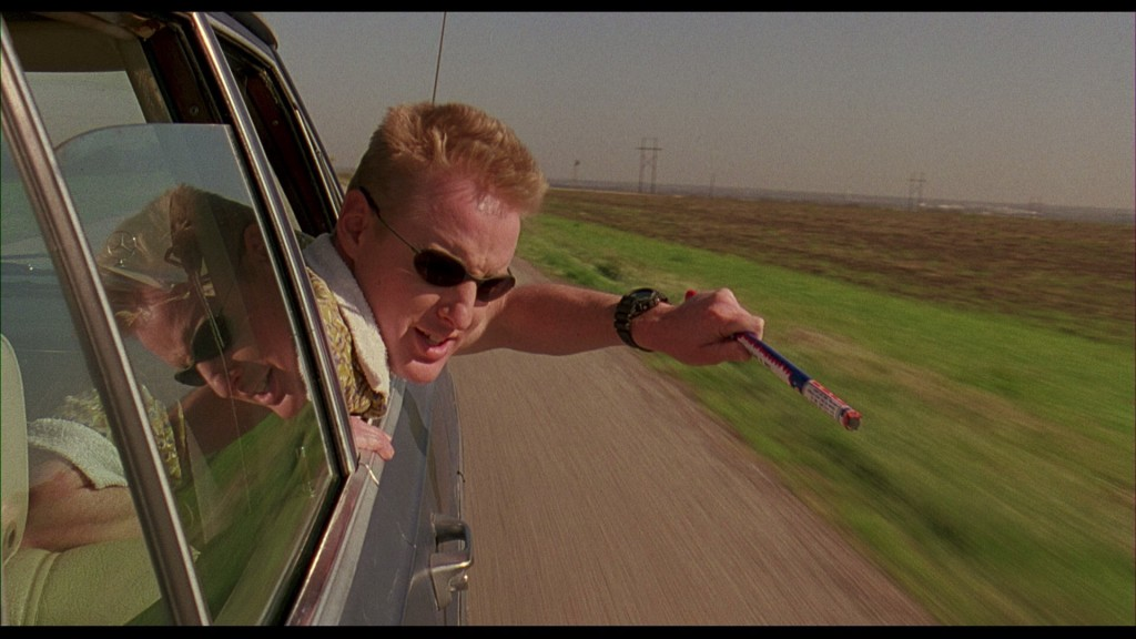 Screencapture from Bottle Rocket. A man fires a firework from the window of a moving car.
