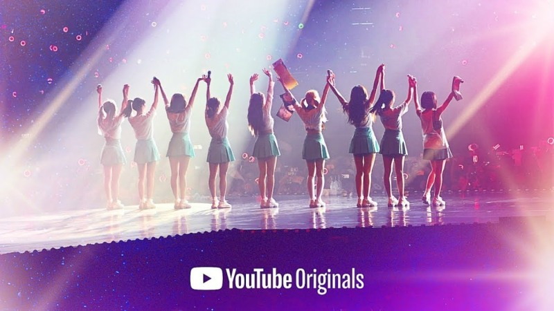 A silhouetted image of TWICE as they bow to their audience onstage.