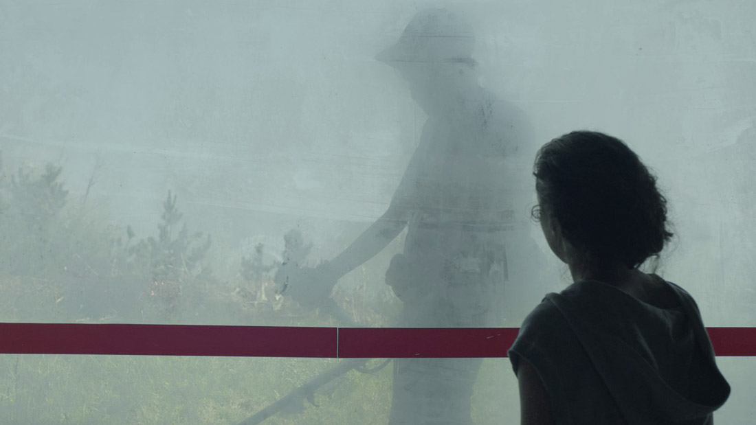 A young girl stares at a young boy mowing the lawn through a fogged window.