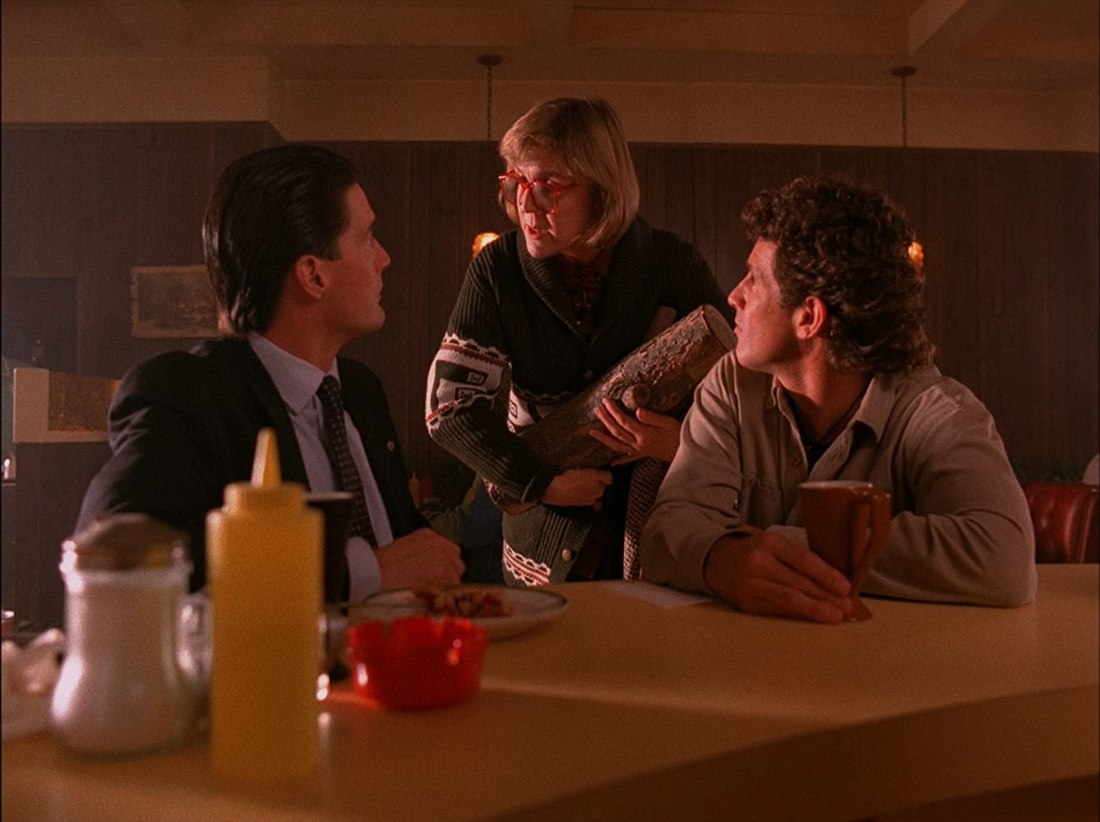 An image from the show Twin Peaks. Drinking coffee in a diner, Agent Cooper and Sheriff Truman turn around to look at a woman cradling a log.
