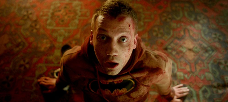 A young man in a batman hoodie is on the ground, framed by ornate carpeting, and is looking up at the camera. There is blood splattered across his face and the front of his hoodie and he is holding himself upright with his hands. He appears surprised.