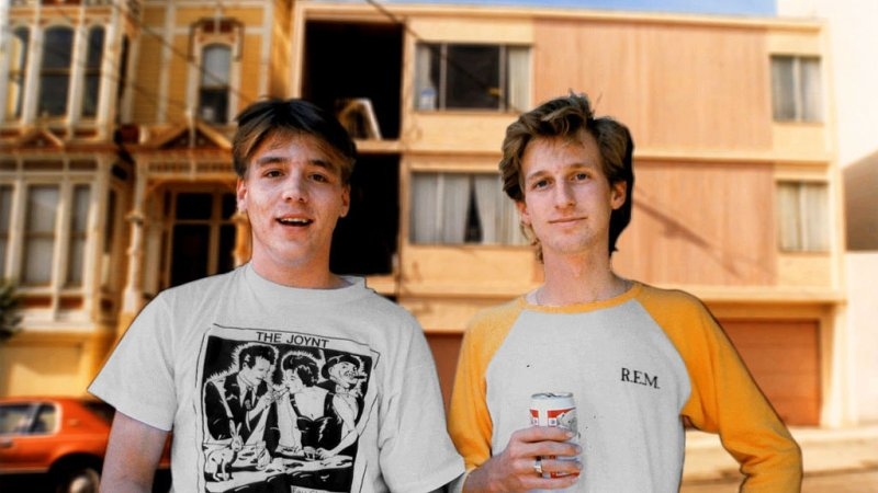 Two young men in band t-shirts stand in front of a run-down pink apartment building. The two men are Mitchell D. and Eddie Lee Sausage, respectively.