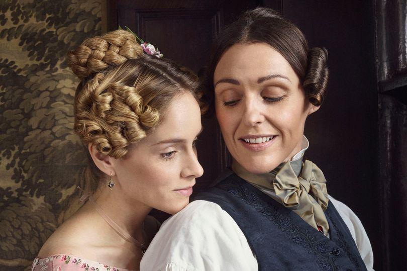 Two women look suggestively at one another. One is stood behind, wearing a pink Victorian dress. The one in front is wearing a waistcoast and bowtie.