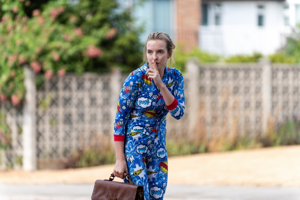 Villanelle has her hand to her lip to signal someone to be quiet. She is holding a brown bag and is wearing blue pyjamas with comic book writing on them.