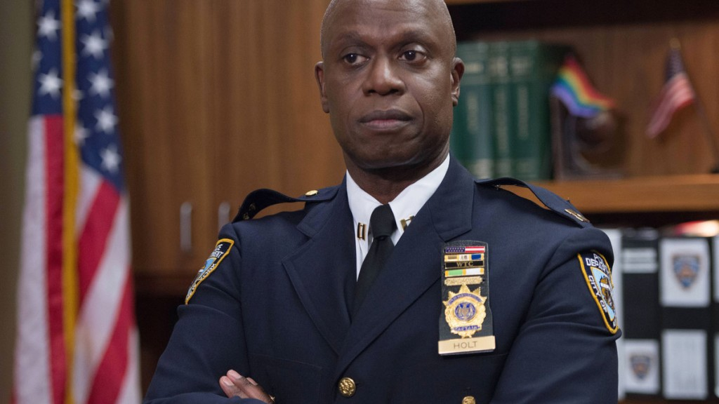 Captain Holt wears his police uniform and stands in his office with his arms folded.