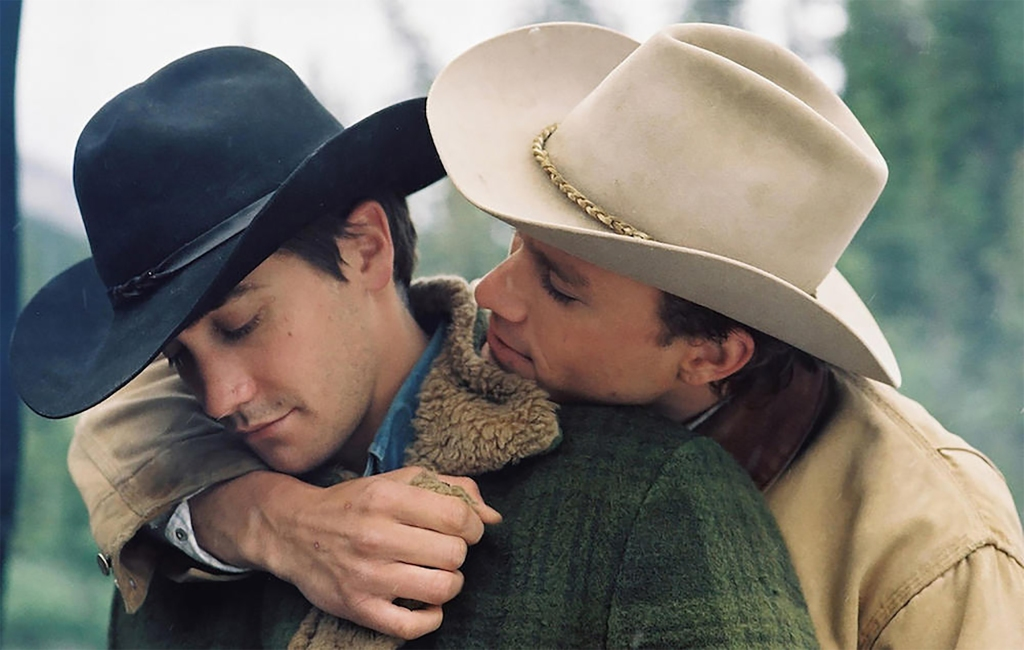 Two men wearing cowboy hands engage in an embrace, with one wrapping his arm around the other.