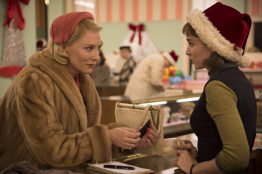 Carol, who is wearing a fur coat, leans over the store counter to talk to Therese, who is wearing a Santa Hat.