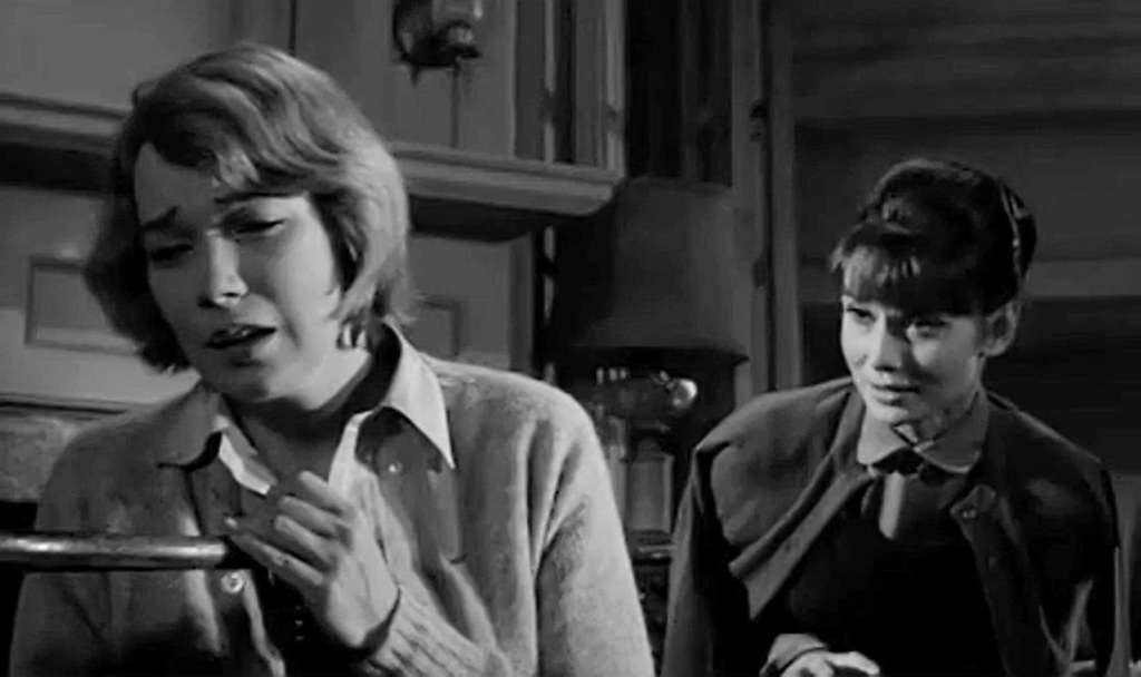 On the left, a blonde woman looks upset. Behind her, another woman tries to console her. The image is in black and white.