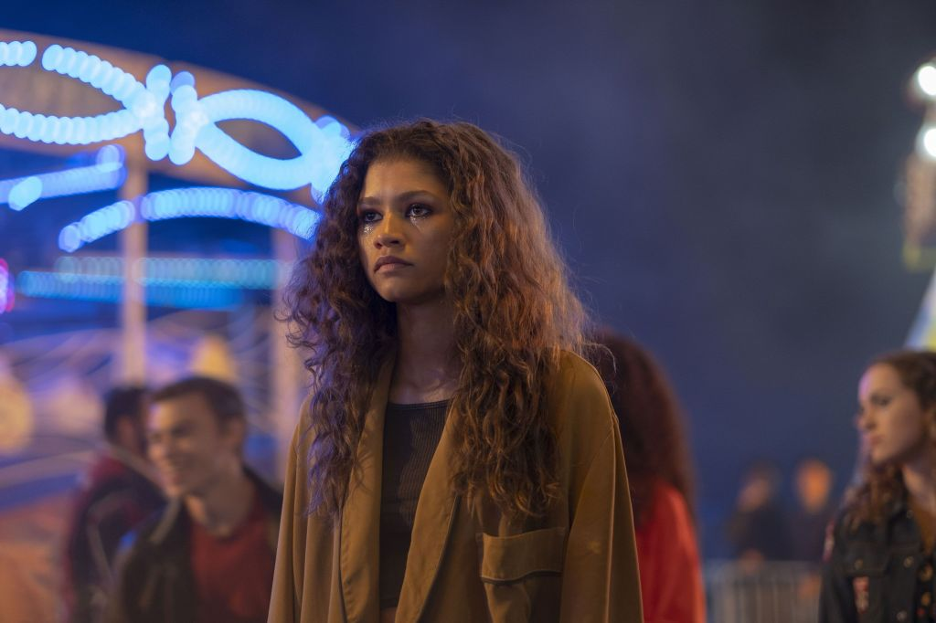Rue stands amongst the crowd at a fairground. She looks distressed.