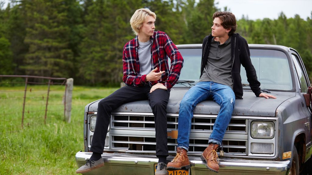 Lukas and Philip sit on the hood of a grey truck in the countryside. They are engaged in coversation.