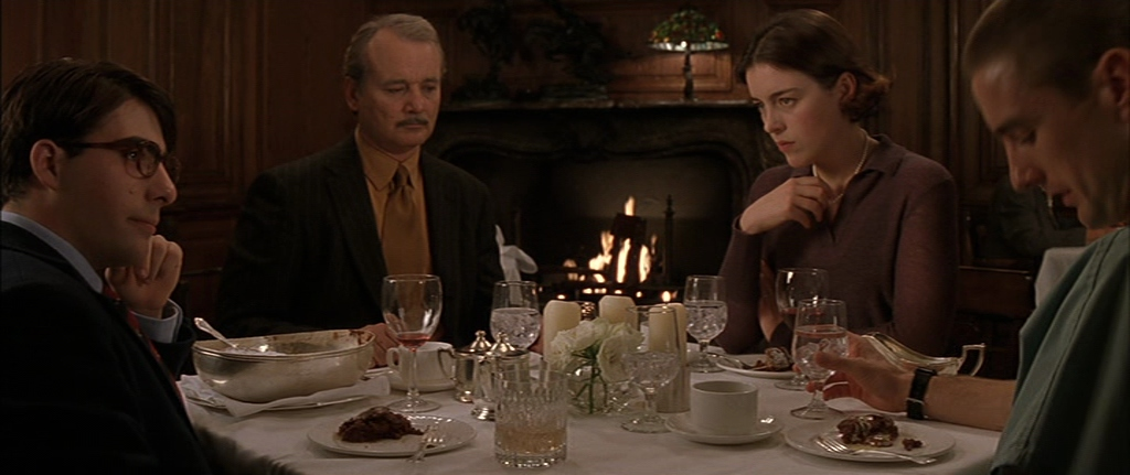 Screencapture from Rushmore. 3 men and a woman sit at a table in a restaurant.