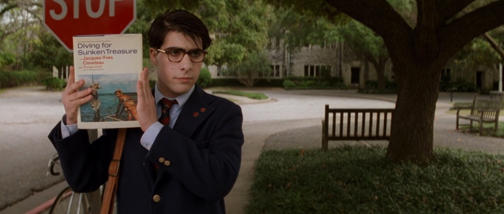 Screencapture from Rushmore. A teenager holds up a book.