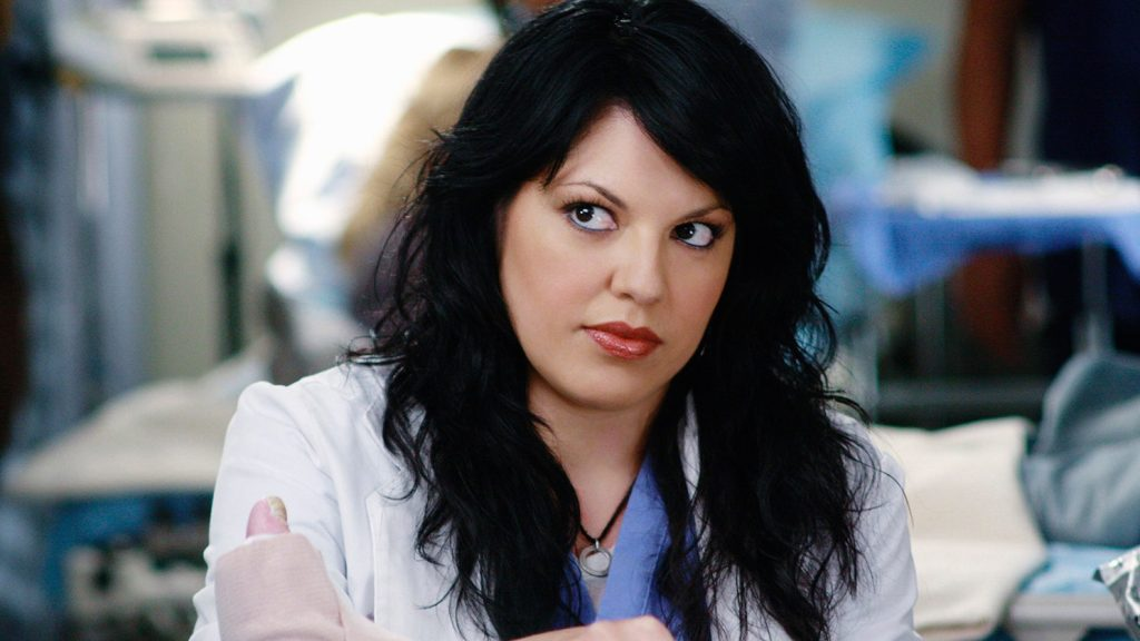 Callie is dressed in a lab coat and scrubs as she works on a patient.