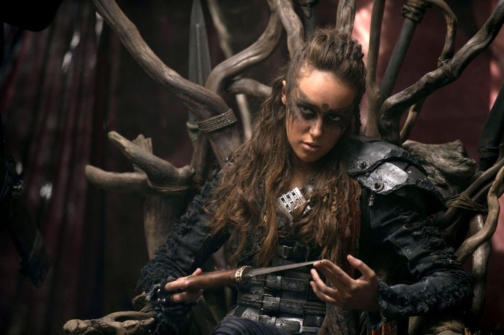 Lexa sits of a throne made of twisted branches. She is wearing dark warpaint over her eyes and is playing with a knife.