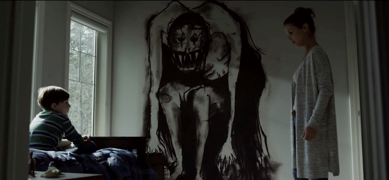 An image from the horror film Z. A woman and son look at each other across the room, and in the middle is a monster painted on the wall.