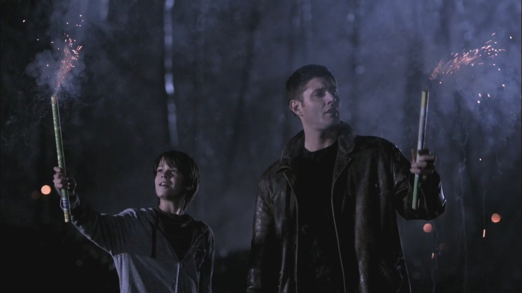 Image of young Sam Winchester and Dean Winchester holding sparklers in a field at night.