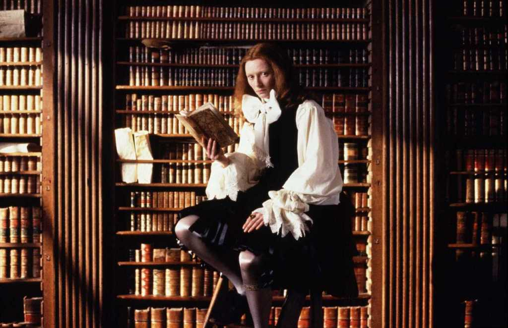 Orlando is reading a book in a library. They are dressed in flamboyant period clothing, with a large white bow and puffed sleeves.