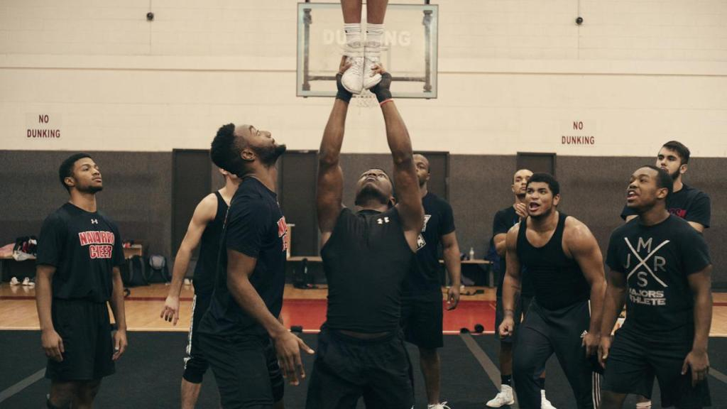 Several men surround Darius - muscular black man - and cheer him on as he holds someone above his head.